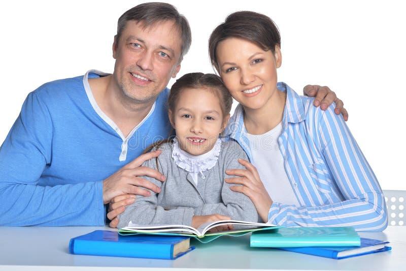 Portret szczęśliwi rodzice i córka robi pracie domowej zdjęcie stock