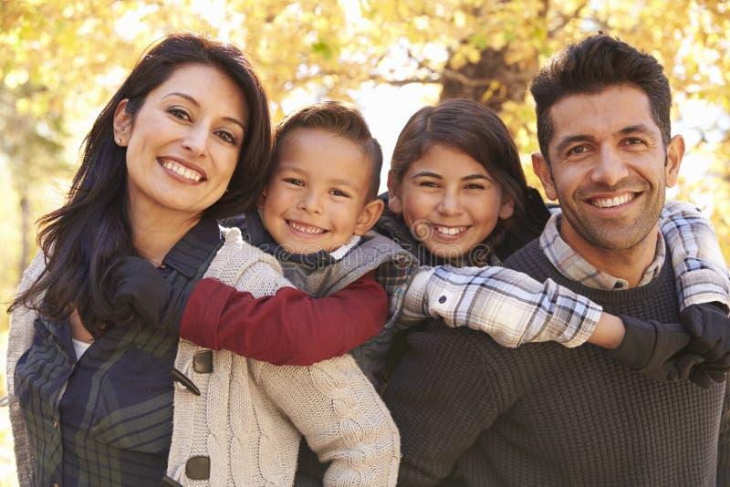 Portret szczęśliwi rodzice piggybacking dzieciaków outdoors fotografia stock
