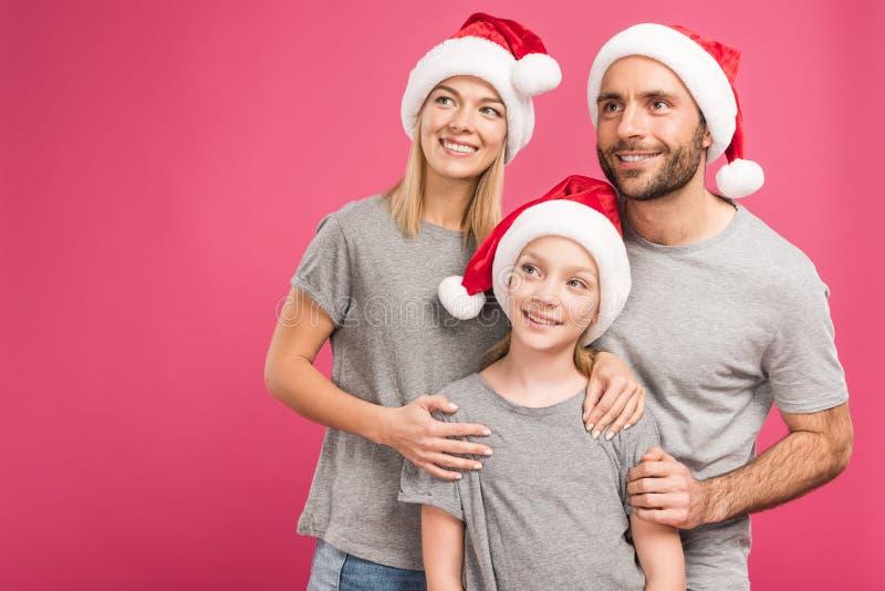 portret szczęśliwi rodzice z uroczą córką w Santa kapeluszach, odizolowywający obraz royalty free