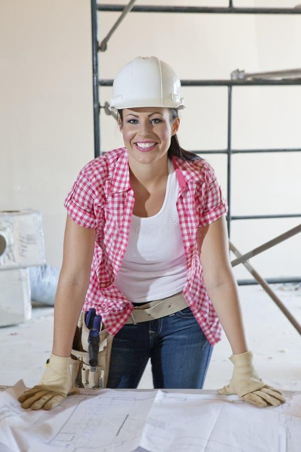 Portret szczęśliwy żeński pracownik budowlany jest ubranym hardhat z projektami zdjęcie stock