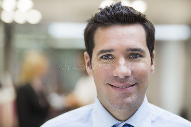Portret szczęśliwy biznesmen pozuje podczas gdy koledzy opowiada wpólnie obraz stock