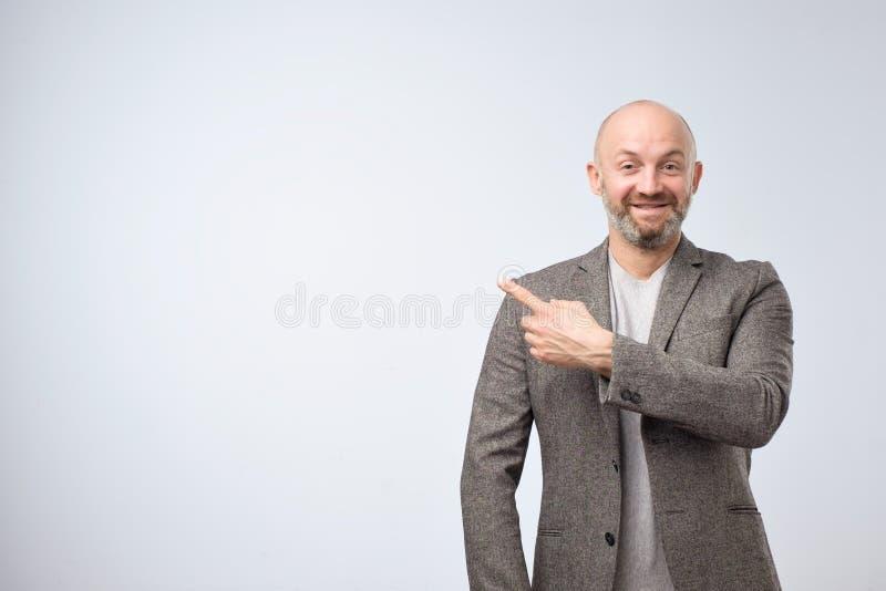 Portret szczęśliwy biznesmen w przypadkowy kostiumu wskazywać palcowy nad białym tłem daleko od fotografia royalty free