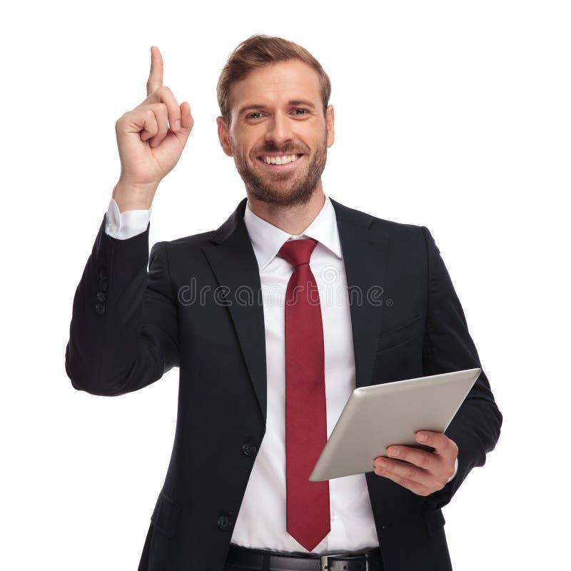 Portret szczęśliwy biznesmen wskazuje palec up z pastylką fotografia royalty free