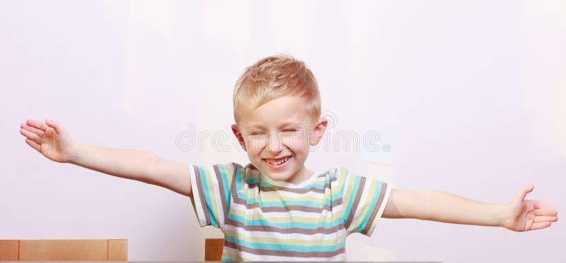 Portret szczęśliwy blond chłopiec dziecka dzieciak z rękami otwiera przy stołem zdjęcie stock
