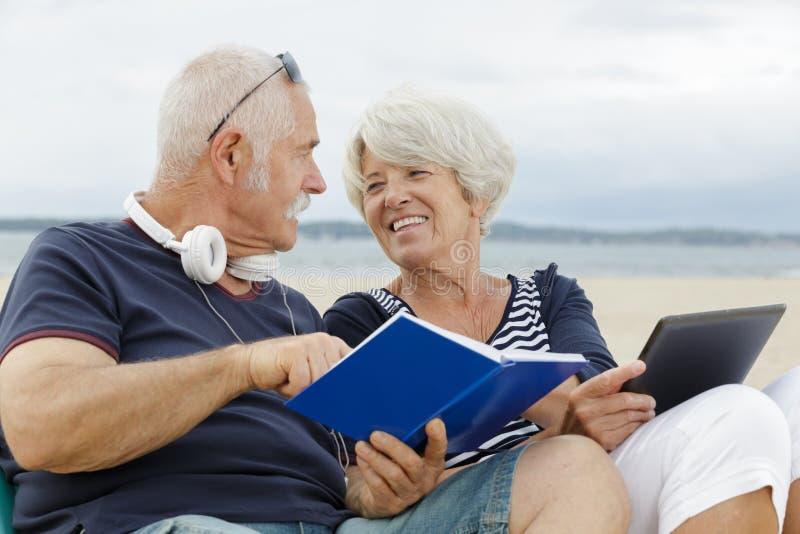 Portret szczęśliwy dorośleć pary czytelniczą książkę outdoors obraz stock