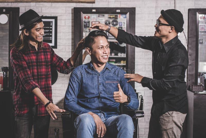 Portret szczęśliwy dwa fryzjer męski z klienta ono uśmiecha się przy fryzjera męskiego sklepem i pozycją fotografia stock