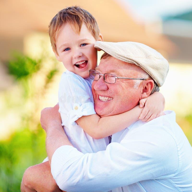 Portret szczęśliwy dziadunio i wnuk obejmuje outdoors fotografia stock