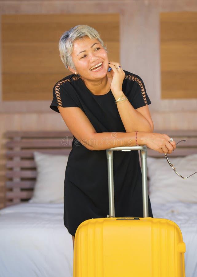 Portret szczęśliwy i atrakcyjny 40s 50s dorośleć Azjatyckiej kobiety przyjeżdża w wakacyjnego pokoju hotelowego z podnieceniem on zdjęcia royalty free