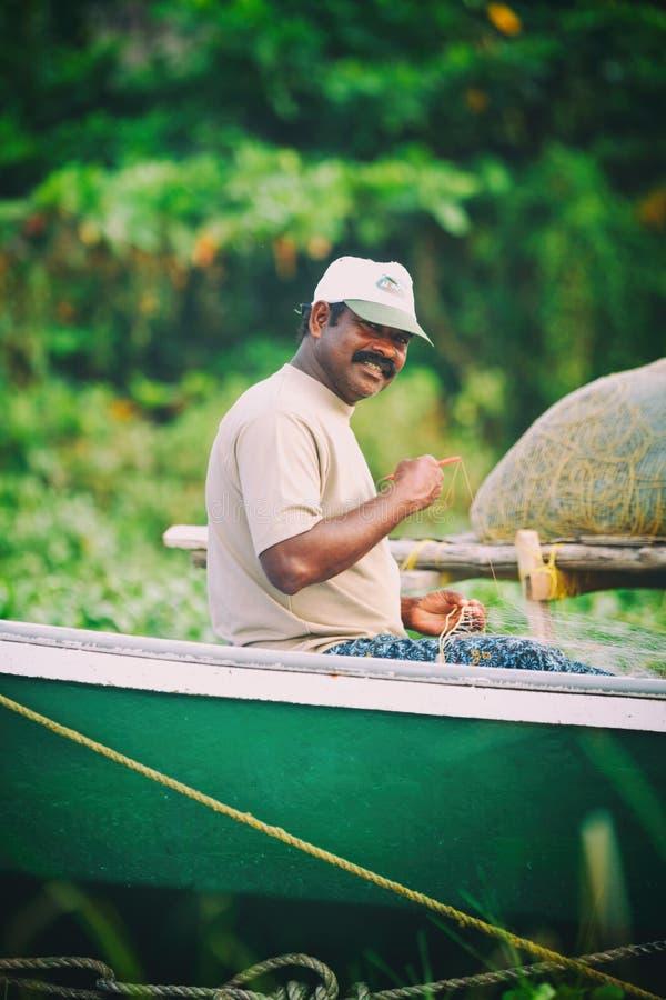 Portret szczęśliwy Indiański rybak rozplątuje sieci rybackie i sprzęt podczas gdy siedzący w łodzi, Kerala India rybołówstwa zato fotografia royalty free