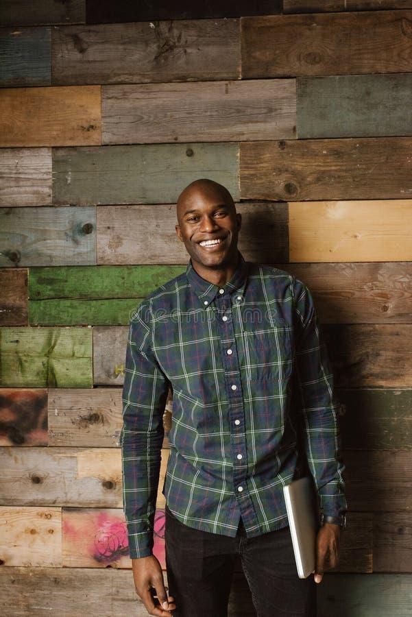 Portret szczęśliwy młody człowiek przeciw drewnianej ścianie zdjęcie stock