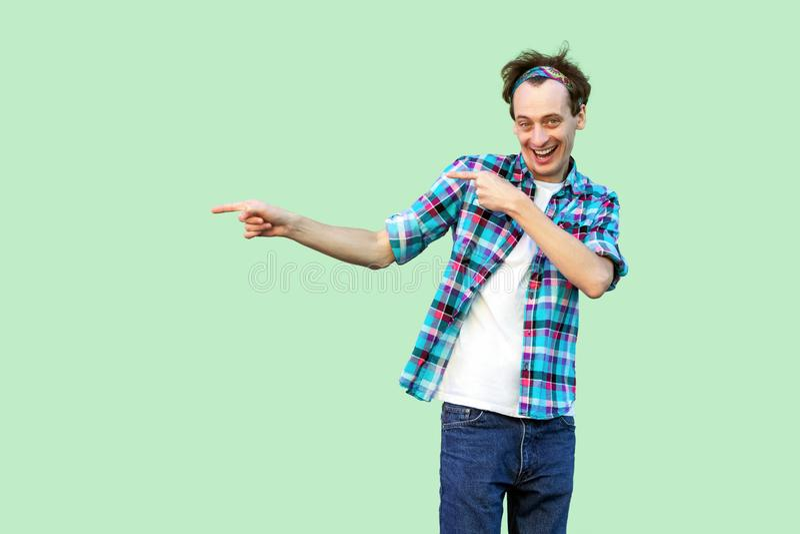 Portret szczęśliwy młody człowiek w przypadkowej błękitnej w kratkę koszula i kapitałki pozycji, patrzejący kamerę, wskazuje przy obrazy royalty free