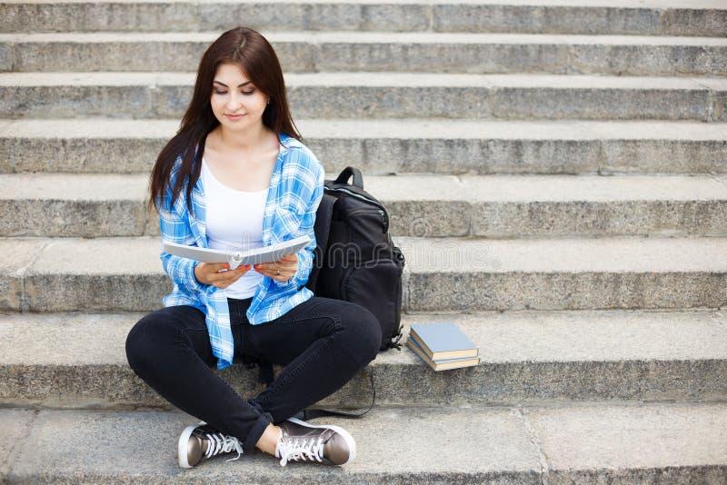 Portret szczęśliwy młody studencki kobiety obsiadanie na miasta stai obrazy stock
