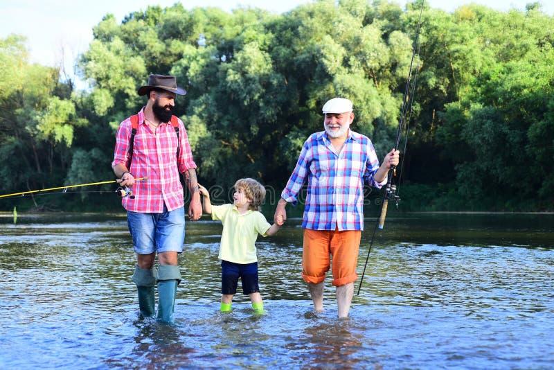 Portret szczęśliwy mały syn, ojciec i dziad, - trzy pokolenia mężczyźni łowi na rzece Szczęśliwy rybak z obrazy royalty free