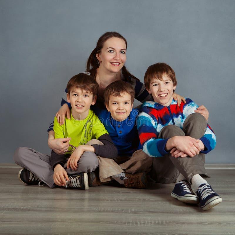 Portret szczęśliwy macierzysty i trzy syna, studio obraz royalty free