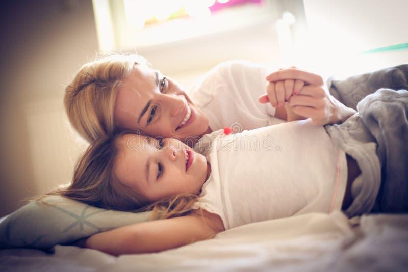 Portret szczęśliwy matki i córki lying on the beach na łóżku zdjęcie royalty free