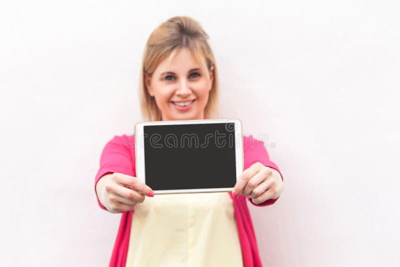 Portret szczęśliwy piękny młody bizneswoman w różowej bluzki pozycji i mienie pastylki pusty ekran z toothy uśmiechem i zdjęcie royalty free
