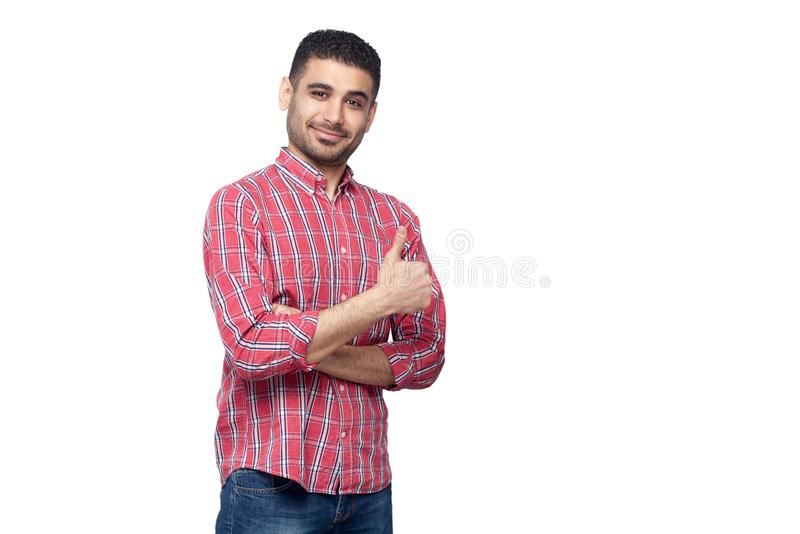 Portret szczęśliwy pomyślny przystojny brodaty młody człowiek w czerwonej w kratkę koszulowej pozycji i patrzeć kamerę z uśmieche obraz stock