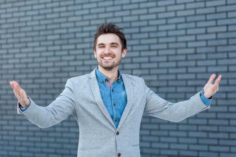 Portret szczęśliwy przystojny brodaty mężczyzna w przypadkowego stylu pozycji z toothy uśmiechem i podnosić rękami, patrzeje kame fotografia royalty free