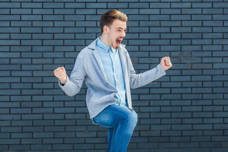 Portret szczęśliwy przystojny młody blondynka mężczyzna w przypadkowego stylu pozycji świętuje jego sukces i raduje się zwycięstw zdjęcie royalty free