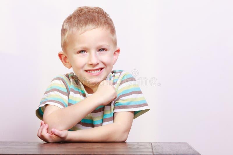 Portret szczęśliwy roześmiany blond chłopiec dziecka dzieciak przy stołem obrazy stock