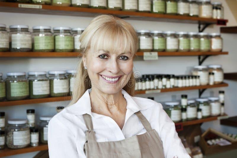 Portret szczęśliwy starszy żeński pracownik w pikantność sklepie obraz stock