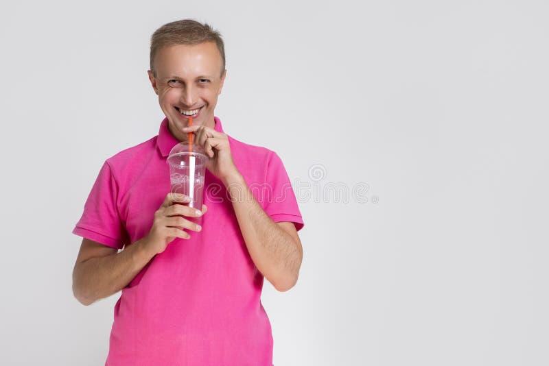 Portret Szczęśliwy Uśmiechnięty Caucasan blondynów mężczyzna Trzyma filiżankę Z Smoothie Pi? Przez s?omy zdjęcia stock