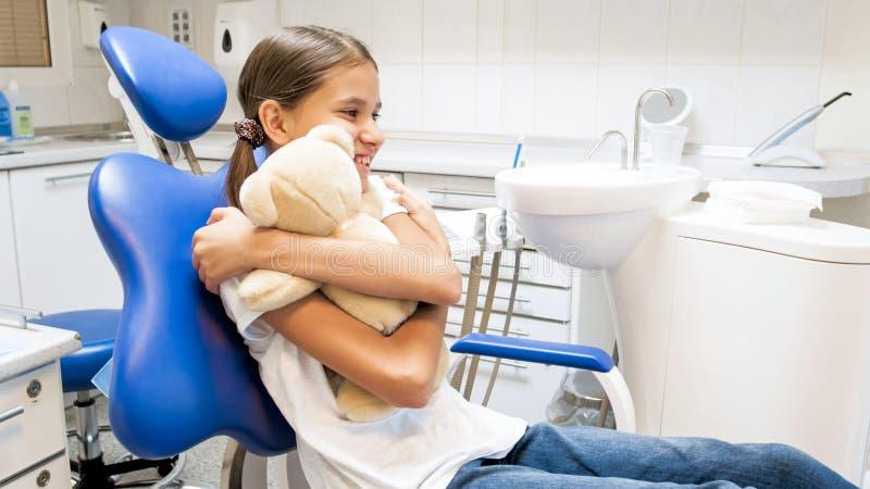 Portret szczęśliwy uśmiechnięty dziewczyny przytulenia miś w dentysty biurze zdjęcie royalty free