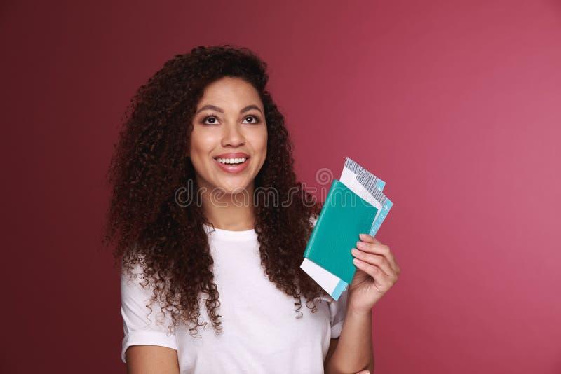 Portret szczęśliwy uśmiechnięty młodej dziewczyny mienia paszport odizolowywający nad tłem podróżni bilety i zdjęcia royalty free