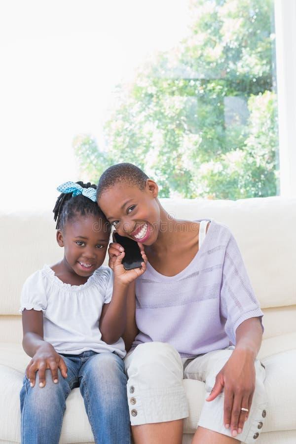 Portret szczęśliwy uśmiechnięty macierzysty telefonowanie z jej córką na leżance zdjęcie stock