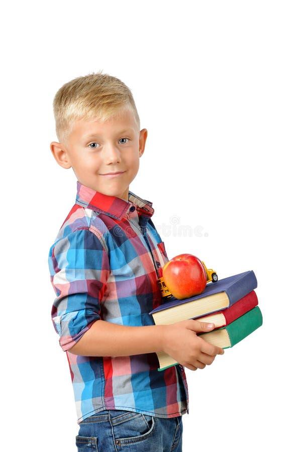 Portret szczęśliwy uczeń z książkami i jabłkiem odizolowywającymi na białym tle Edukacja fotografia royalty free