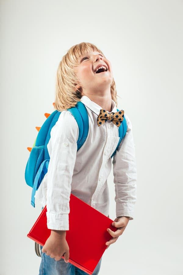 Portret szczęśliwy uczeń z książkami i jabłkiem odizolowywającymi na białym tle Edukacja, odizolowywająca fotografia royalty free