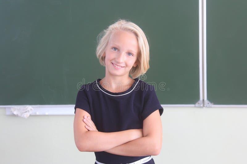 Portret szczęśliwy uczennicy 9-11 lat w sala lekcyjnej blisko chalkboard tylna szkoły zdjęcia royalty free