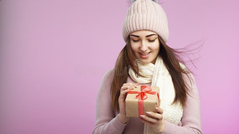 Portret szczęśliwy zdziwiony dziewczyny otwarcia prezenta pudełko w dekoracyjnym rzemiosło papierze, młodej kobiecie w trykotowym zdjęcia stock