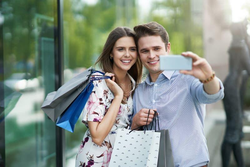 Portret szcz??liwa para z torbami na zakupy w mie?cie ono u?miecha si? i huging zdjęcia stock