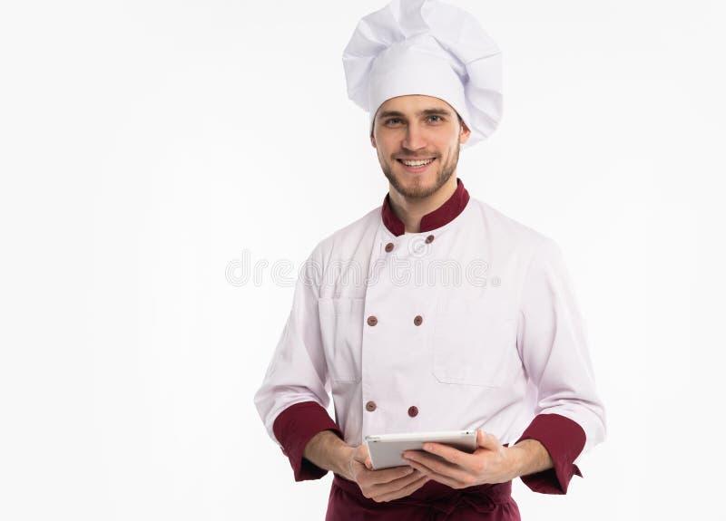 Portret szcz??liwego m?skiego szefa kuchni pastylki kucbarski pokazuje pusty ekran komputerowy odizolowywaj?cy na bia?ym tle obrazy stock