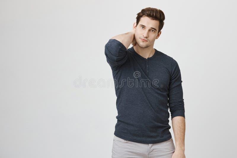 Portret szczupły przystojny mężczyzna drapa jego szyję i patrzeje kamerę czuje unconfident, odosobnionego nadmiernego biel, zdjęcie stock