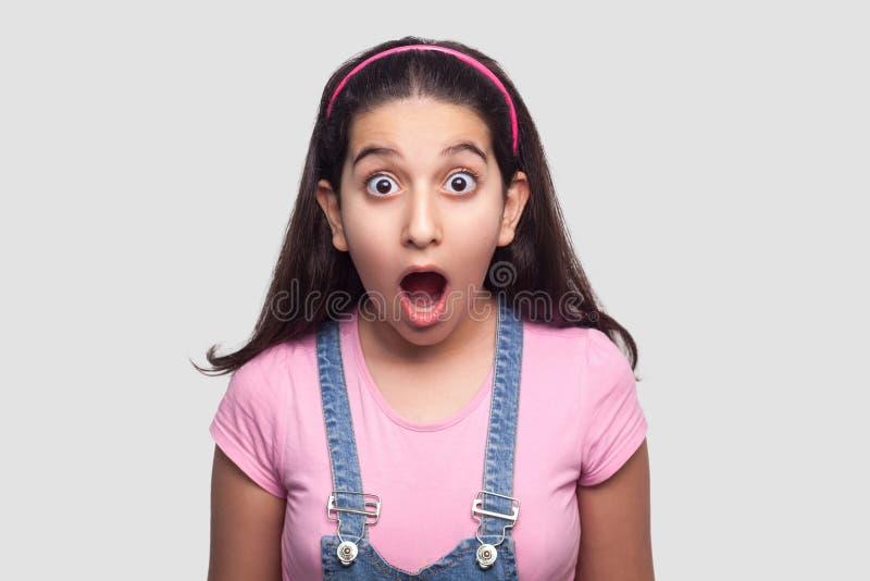 Portret szokująca brunetki młoda dziewczyna w przypadkowym stylu, różowej koszulce i błękitnych kombinezonach, stoi z dużymi ocza obrazy royalty free