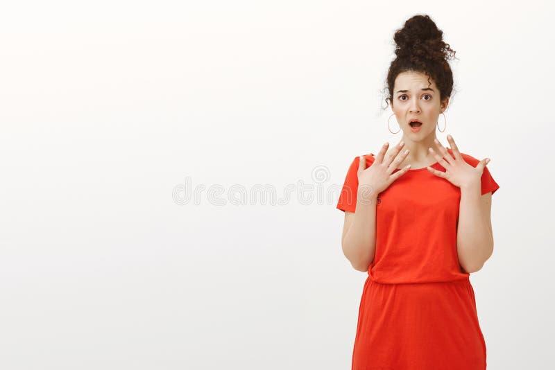 Portret szokująca ogłuszona atrakcyjna europejska kobieta w przypadkowej czerwieni sukni, dyszący z rozpieczętowanym usta, trzyma zdjęcia stock