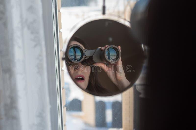 Portret szpieguje na sąsiad zdziwiona brunetka z lornetkami przyglądającymi out okno, obraz stock