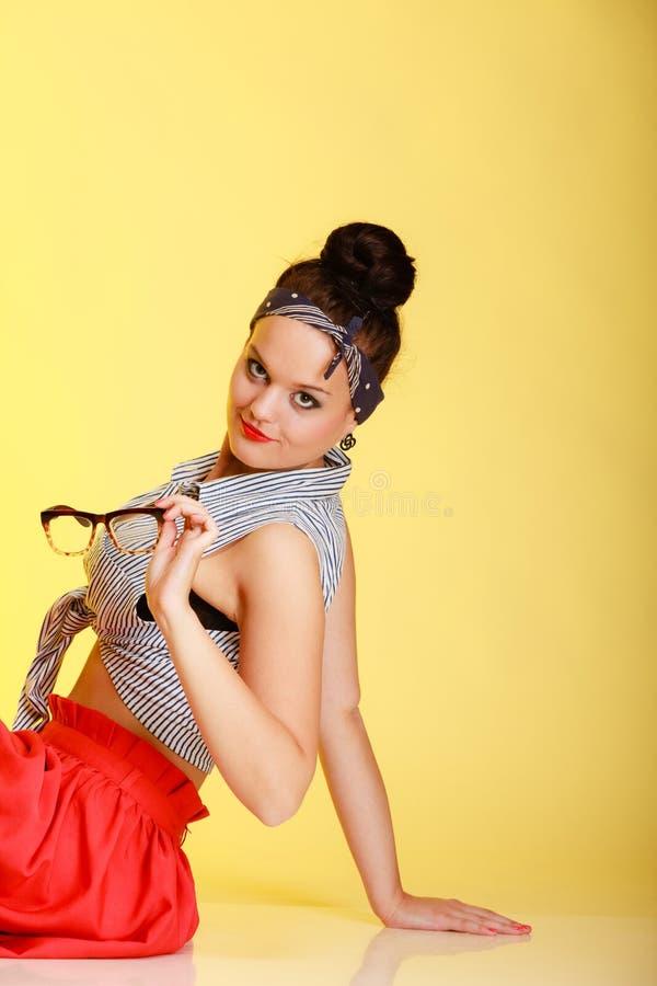 Portret szpilki modna dziewczyna z szkłami i babeczką na kolorze żółtym zdjęcie royalty free
