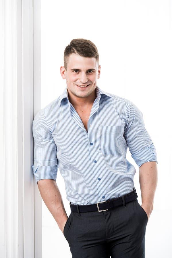 Portret toevallige jonge mens die tegen het kader van een open deur op lichte en achtergrond die aan camera leunen glimlachen eru stock foto's