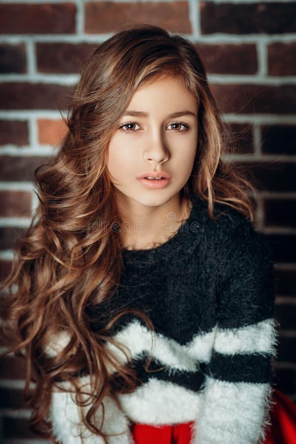 Portret trochę ładna moda dzieciaka dziewczyna z długim skarbikowanym włosy na cegły ściany tle zdjęcie stock