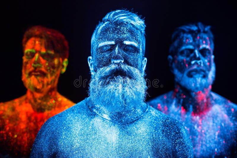 Portret trzy brodatego mężczyzny malował w fluorescencyjnych proszkach obrazy stock