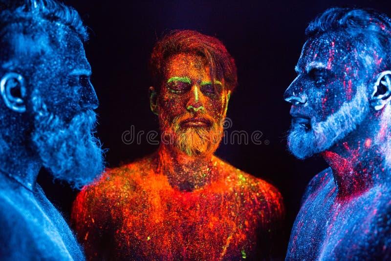 Portret trzy brodatego mężczyzny malował w fluorescencyjnych proszkach fotografia stock