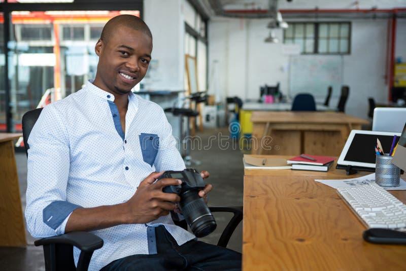 Portret trzyma cyfrową kamerę przy biurkiem męski projektant grafik komputerowych zdjęcie stock