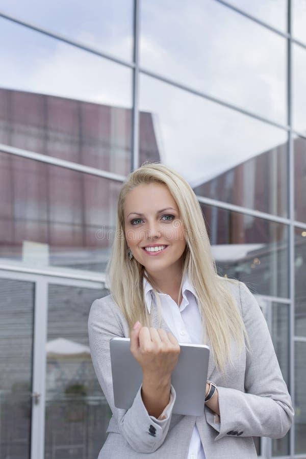 Portret trzyma cyfrową pastylkę przeciw budynkowi biurowemu szczęśliwy bizneswoman zdjęcie royalty free