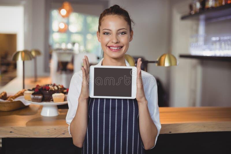 Portret trzyma cyfrową pastylkę przy kontuarem kelnerka fotografia royalty free