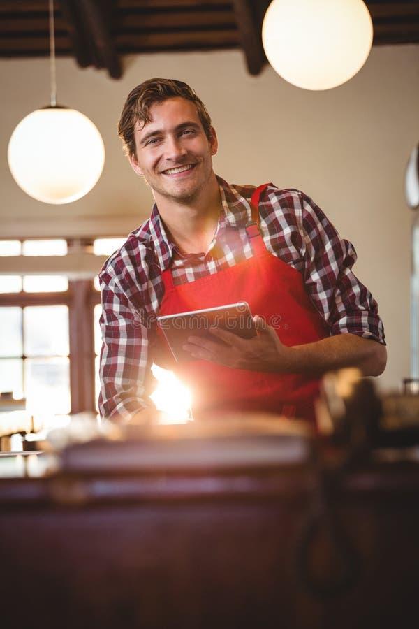 Portret trzyma cyfrową pastylkę uśmiechnięty kelner zdjęcia royalty free