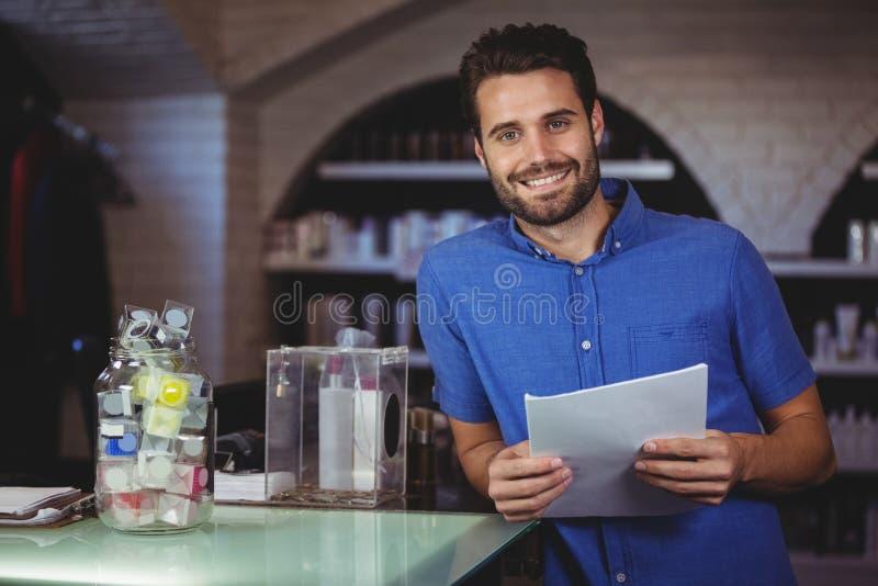 Portret trzyma formę przy włosianym salonem męski fryzjer fotografia stock