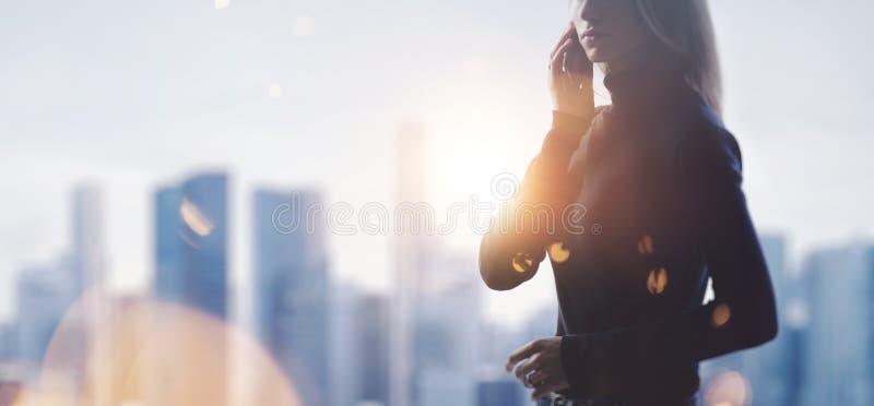 Portret trzyma jej smartphone w młoda kobieta ręki Zamazany miasto na tle szeroki obraz stock